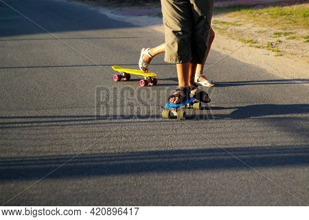 Defocus Children Playing On Skateboard In The Street. Caucasian Kids Riding Penny Board, Practicing