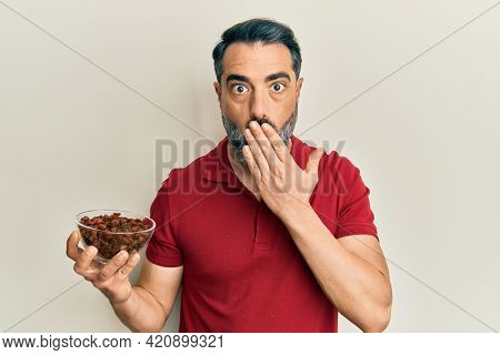 Middle age man with beard and grey hair holding raisins bowl covering mouth with hand, shocked and afraid for mistake. surprised expression