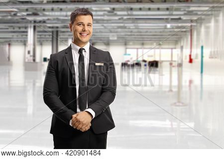Airport official in a suit and tie posing inside a terminal building