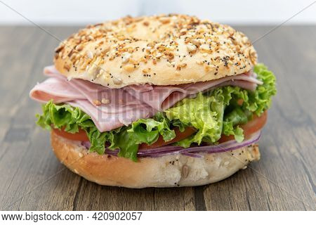 Everything Bagel Bun Envelops This Non Traditional Ham Sandwich Loaded With Lettuce, Meat Slices, An