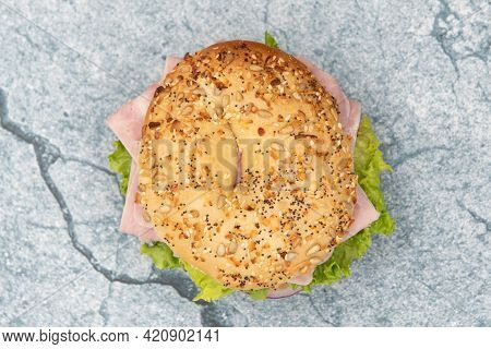 Overhead View Of Everything Bagel Bun Envelops This Non Traditional Ham Sandwich Loaded With Lettuce