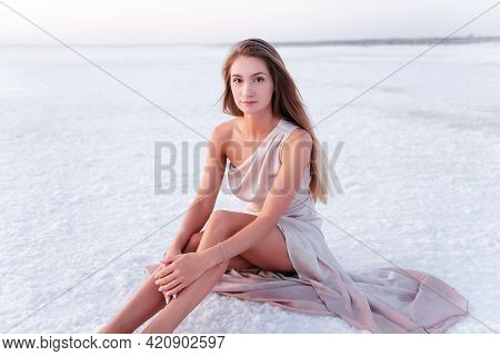 Young Blonde Woman In An Evening Airy Pastel Pink Powdery Dress Sitting Barefoot On White Crystalliz
