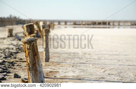 White Gound Or Salt Lake. Remains Of A Wooden Building In A Salt Lake. Rotten Wooden Posts. Extracti