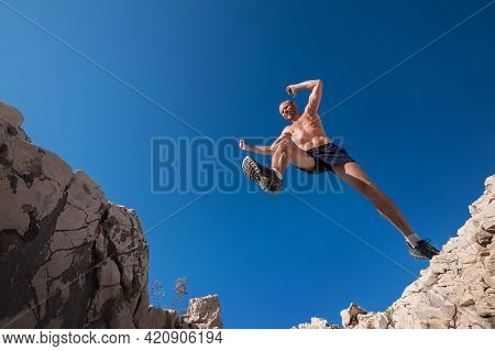 Active Fast Running Mountain Sky Runner Smiling And Jumping Over The Cleft Cliff During The High Mor