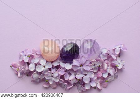 Lilac Flowers  And Gemstones Minerals. Amethyst And Rose Quartz On Pink Background. Magic Rocks For