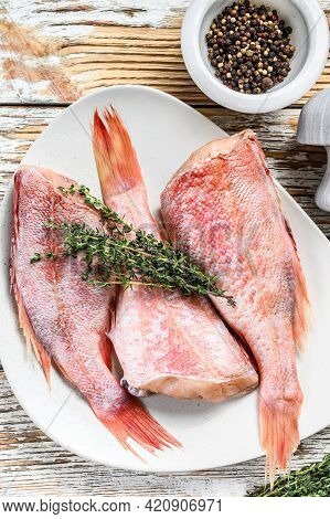Whole Raw Red Perch Or Sea Bass Fish On A Plate. White Wooden Background. Top View