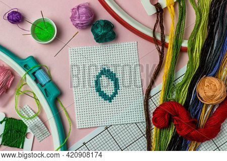 Green Number 0 Cross-stitch Embroidered Surrounded By Accessories For Embroidery: Threads Of Moulin