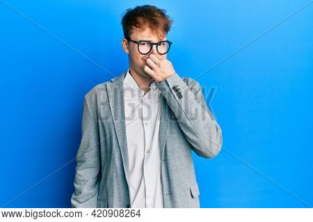 Young caucasian man wearing elegant clothes and glasses smelling something stinky and disgusting, intolerable smell, holding breath with fingers on nose. bad smell