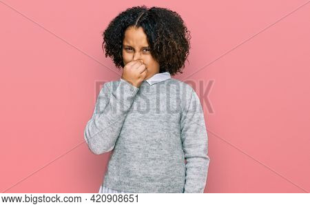 Young little girl with afro hair wearing casual clothes smelling something stinky and disgusting, intolerable smell, holding breath with fingers on nose. bad smell