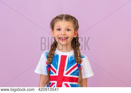A Little Beautiful Girl With Pigtails In A T-shirt With The Image Of The English Flag Smiles.