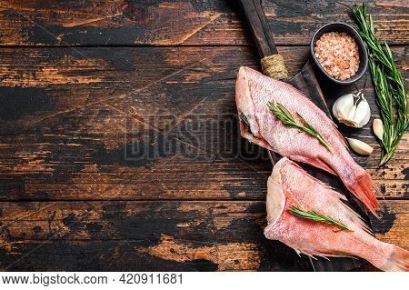 Whole Raw Fresh Red Perch Or Seabass Fish. Dark Wooden Background. Top View. Copy Space