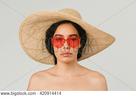 Bare chested woman wearing a big round hat and red vintage heart-shaped sunglasses