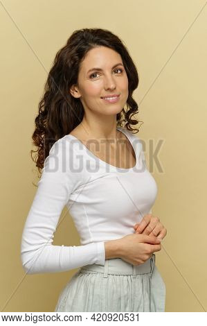 Portrait Of Millennial Softly Smiling Woman Dressed In White Posing Over Cream Wall. Natural Beauty,
