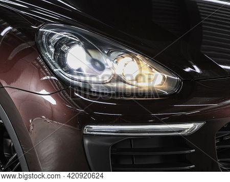 Novosibirsk, Russia - May 16, 2021: Porsche Cayenne, Headlight Of A Modern Popular Car Close-up. Shi