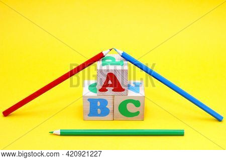The Letters Of The English Alphabet Abc On Wooden Toy Blocks On A Yellow Background. Colored Pencils