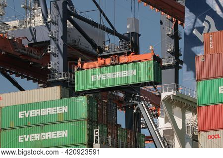 Rotterdam, The Netherlands - Circa 2019: Containers being unloaded from a huge cargo ship in the Euromax container terminal of the Port of Rotterdam. Gantry cranes work lifting Evergreen containers