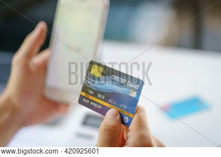 Man Using Smartphone And Mock Up Credit Card For Shopping Online. Pays For Purchase.online Payment,b