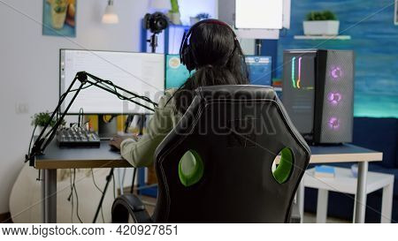 Back Shot Of Streamer Woman Playing On Powerful Computer Shooter Video Game For Tournament, Talking
