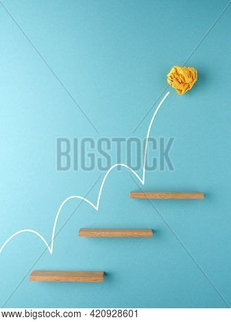 Yellow Crumpled Paper Ball Bounces Up Stairs, Success Or Creativity Concept
