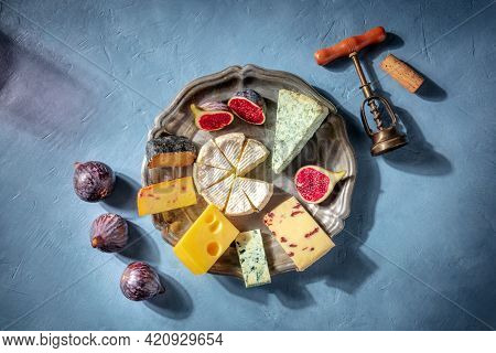 Cheese And Wine. A Cheeseboard With Brie, Blue Cheese And Other Sorts, With A Corkscrew And A Cork,