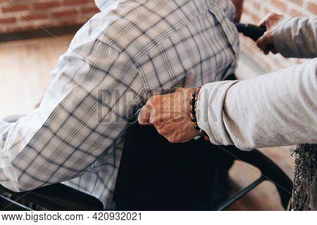Wife pushing her husband#39;s wheelchair