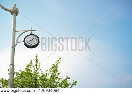 Clock Hanging On A Vintage Pole, Outdoors On A Sunny Day, Blue Clear Sky Background. Black Dial Show