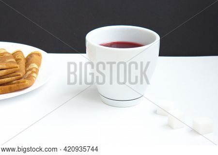 Red Hibiscus Tea In A White Cup With Delicious Pancakes On A Plate And Pieces Of Refined Sugar On Bl