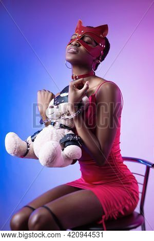 Black Woman In A Bdsm Cat Mask In Handcuffs With A Teddy Bear In Her Hands