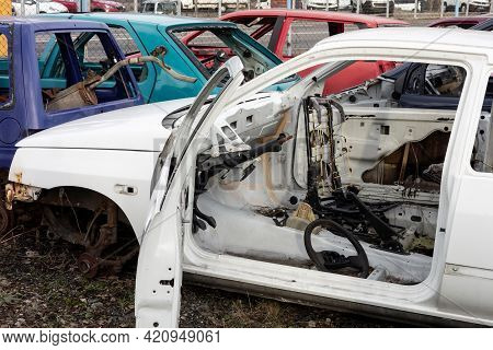 An Old White Wreck Car With Open Door In A Scrap Yard That Were Cleared From Interior And Are Prepar