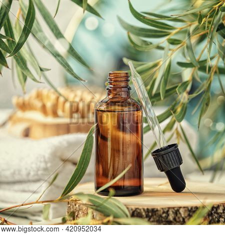 Amber glass bottle with wooden massage brush, eucalyptus leaves, mirror and towels. Natural organic eco cosmetic packaging, luxury beauty products for body care