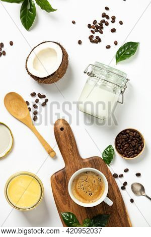 Ingredients for paleo style and ketogenic bulletproof coffee: coconut oil, butter, coffee, flat lay, top view