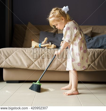 Adorable Little Girl With Golden Hair In Polka Dot Linen Dress Sweeping Floor With Broom, Helping Mo