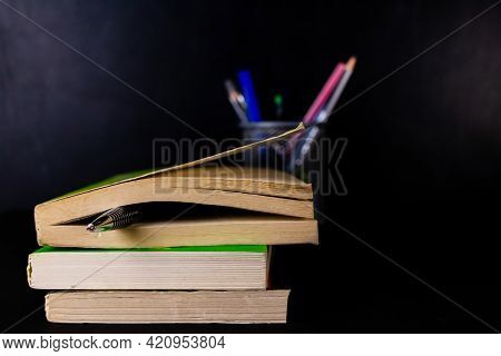 Front Close Up Shot Of A Pen Put In Closed Book With Black Board And A Pen-stand Blurred In The Back