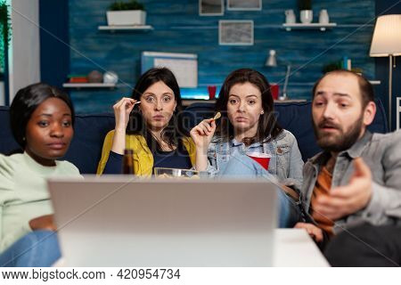 Multi-ethnic Friends Watching Online Film On Laptop Computer Relaxing On Couch Together. Group Of Mu