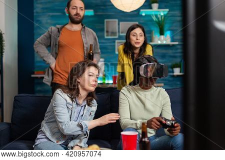 Multi Ethnic Friends Socialising Playing Video Games Experiencing Virtual Reality Using Headset. Mix