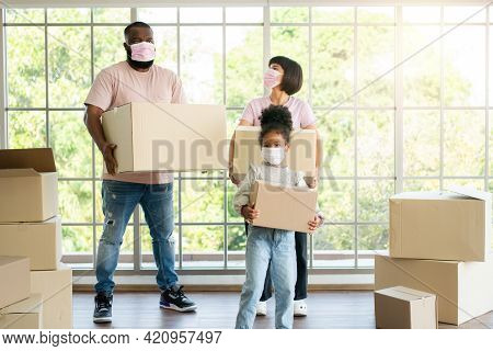 Mixed Race Families Are Carrying Cardboard Boxes And Walking From The Front Door Into The House In A