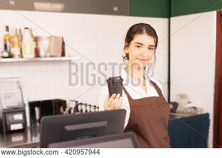 Beautiful Caucasian Barista Woman Show Takeaway Coffee Cup In One Hand At Coffee Bar. Barista Work A