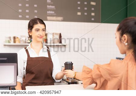Beautiful Caucasian Barista Woman Give Takeaway Coffee Cup To Customer And Customer Receiving Coffee