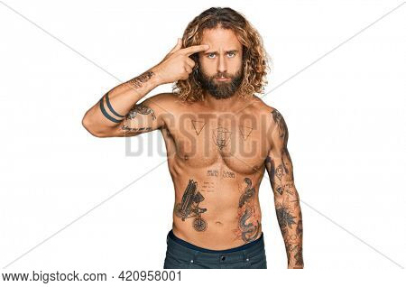 Handsome man with beard and long hair standing shirtless showing tattoos pointing unhappy to pimple on forehead, ugly infection of blackhead. acne and skin problem
