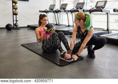 Female Trendy Personal Trainer Holding Young Fit Attractive Female Clients Feet And Assisting During
