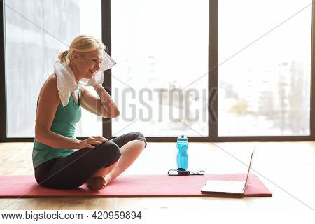 Beautiful Mature Woman Smiling And Wiping Her Forehead With Towel After Intensive Workout At Home, S