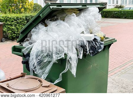 Green Garbage Container Bin Overflowing With Plastic Packaging Waste