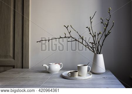 Minimalistic Scandinavian Style. Half-open Branches Of An Apple Tree In A White Fluted Vase. A Kettl