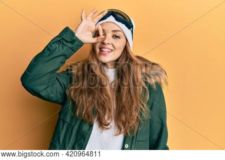 Beautiful blonde caucasian woman wearing snow wear and sky glasses smiling happy doing ok sign with hand on eye looking through fingers