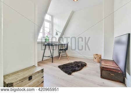 Minimalist Style Home Workplace With Table And Chair Placed Near Window In Small Attic Room With Old