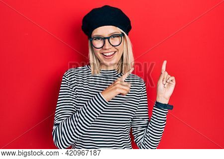 Beautiful blonde woman wearing french look with beret an glasses smiling and looking at the camera pointing with two hands and fingers to the side.