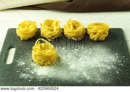 Twisted Noodles And Flour On The Table. Tagliatelle Pasta In The Form Of A Nest On A Cutting Board.