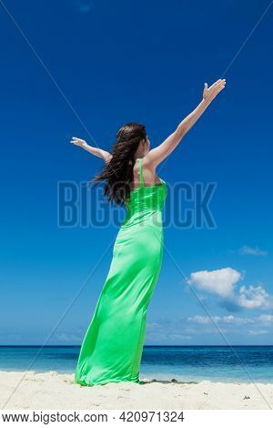 Happy woman enjoy summer vacation on beach standing with raised hands