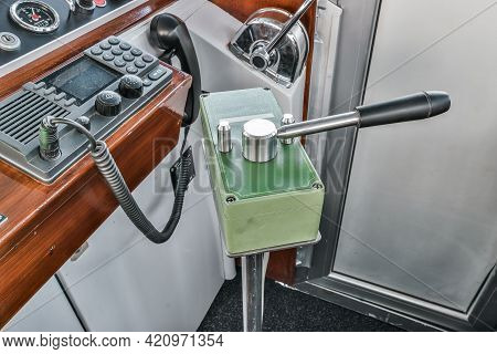 From Above Steering Lever Located Near Dashboard With Radio In Cockpit Of Contemporary Ship