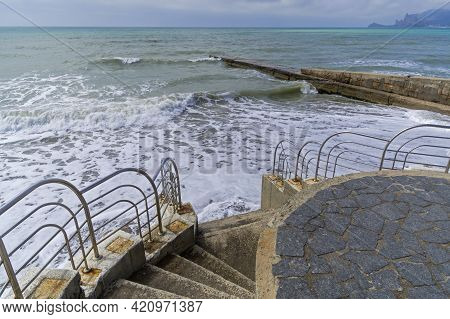 Staircase Descending To The Sandy Beach. A Strong Surf Reaches The Lower Steps. Sudak, Crimea. End O